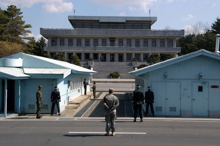 Photo: A view in May 2007 from South Korea towards North Korea in the Joint Security Area at Panmunjom. North and South Korean military personnel, as well as a single US soldier, are to be seen. Credit: Wikimedia Commons.
