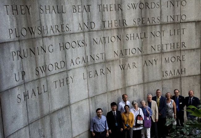 "Faith groups' representatives in front of the Isaiah Wall across the street from the United Nations Building in New York City with the Bible verse ""...they shall beat their swords into plowshares, and their spears into pruning hooks: Nation shall not lift up sword against nation, neither shall they learn war any more."" Credit: ICAN"