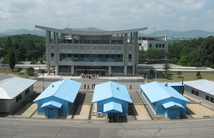 Photo: The Conference Row in the Joint Security Area of the Korean Demilitarized Zone, looking into South Korea from North Korea. It shows guards on both sides and a group of tourists in the South. Created: 26 July 2012. Credit: Wikimedia Commons.